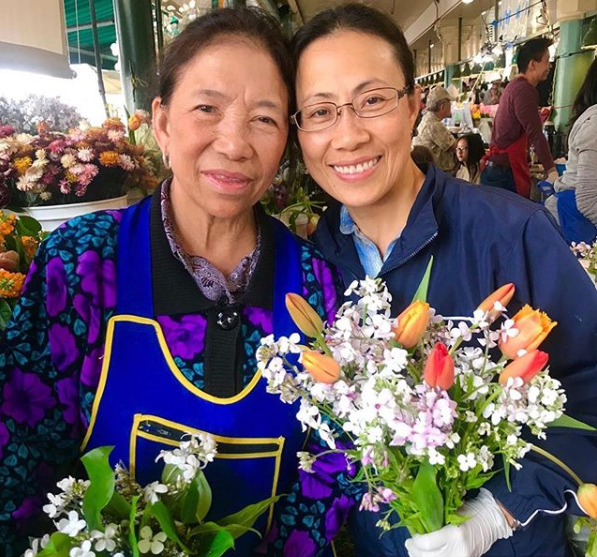 Two women holding flowers at the Pike Place Market